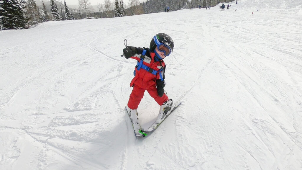 Kid learning to ski down slope